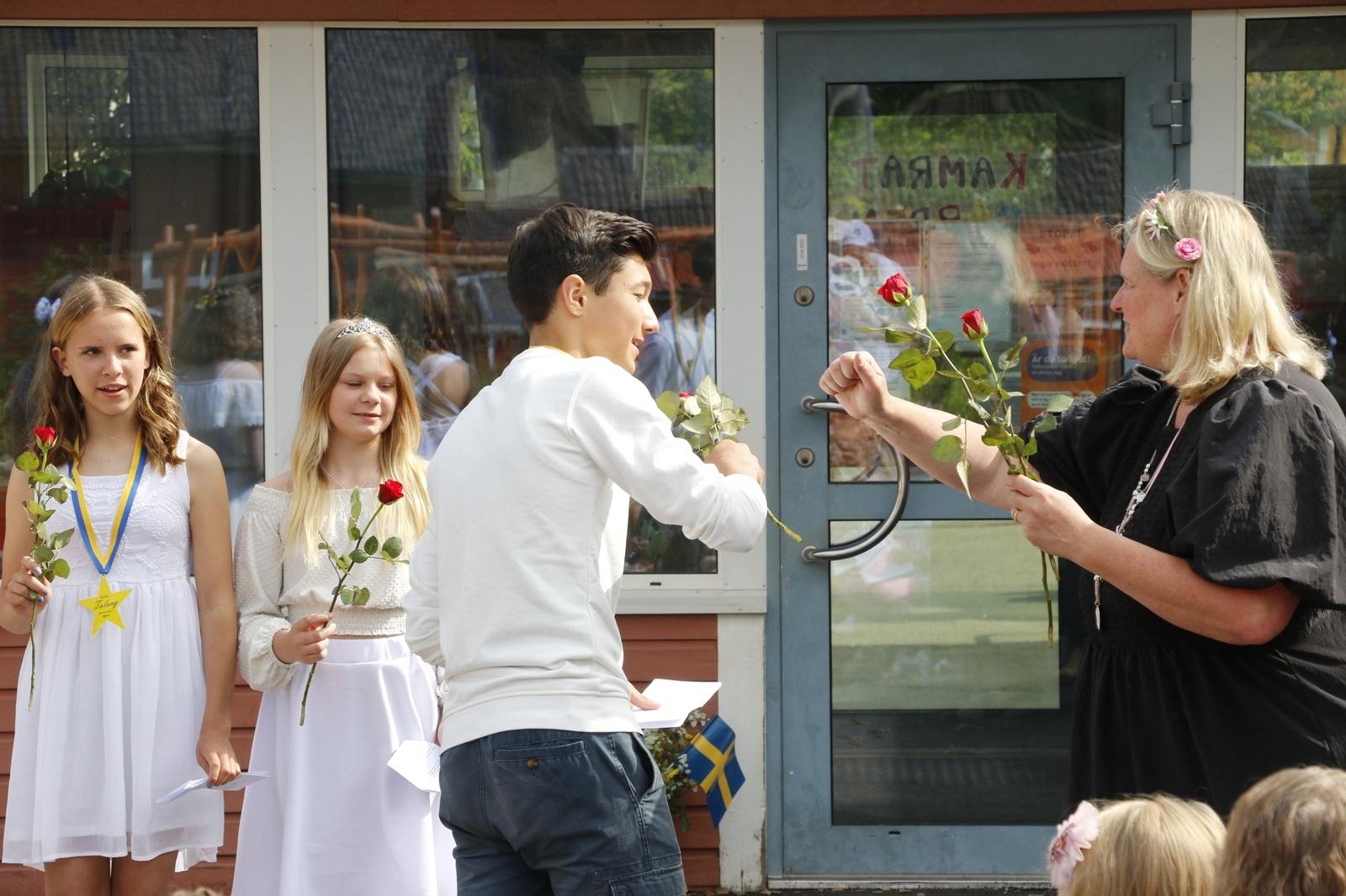 Sexorna tackas av med en ros och rektor Anna Andersson kör med coronasäker handskakning.