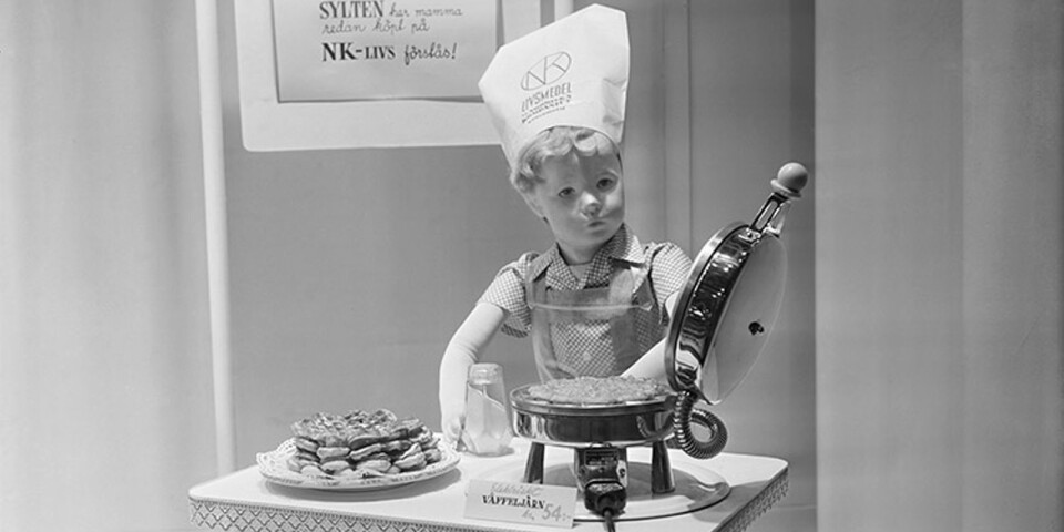 NK:s skyltfönster, 1950. En liten pojke som skyltdocka och som lagar våfflor. Han har kockmössa med NK Livs logotyp.