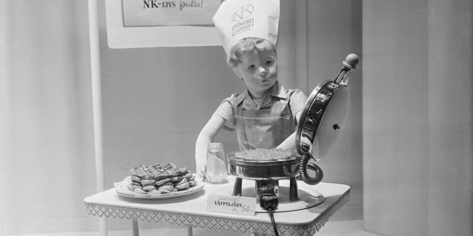 NK's window in 1950. A dummy, in the shape of a little boy, making waffles.He is wearing a chef's toque with the NK food hall's logo.