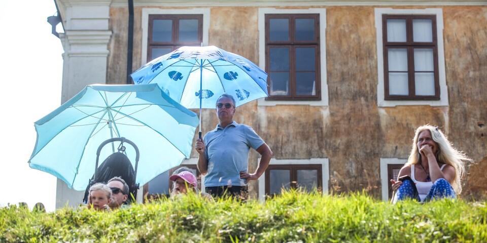 Publiken hukade under paraplyer för att få skydd från den gassande solen.