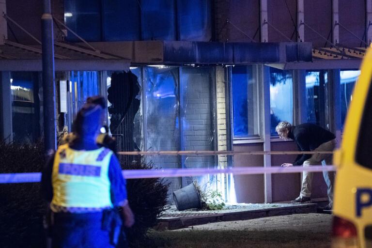 Polis och bombtekniker undersöker den skadade entrén.