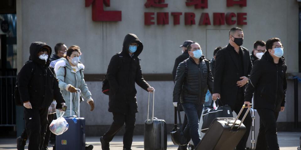 Människor utanför en tågstation i Peking.