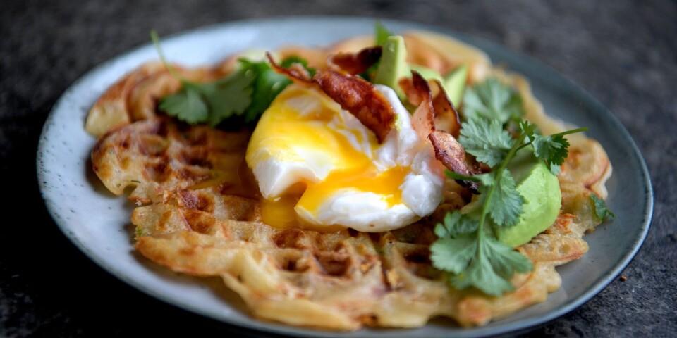 Frasvåfflor modell extra allt. Här smaksatta med knaperstekt bacon, ost och chili och serverade med pocherat ägg, avokado och koriander.
