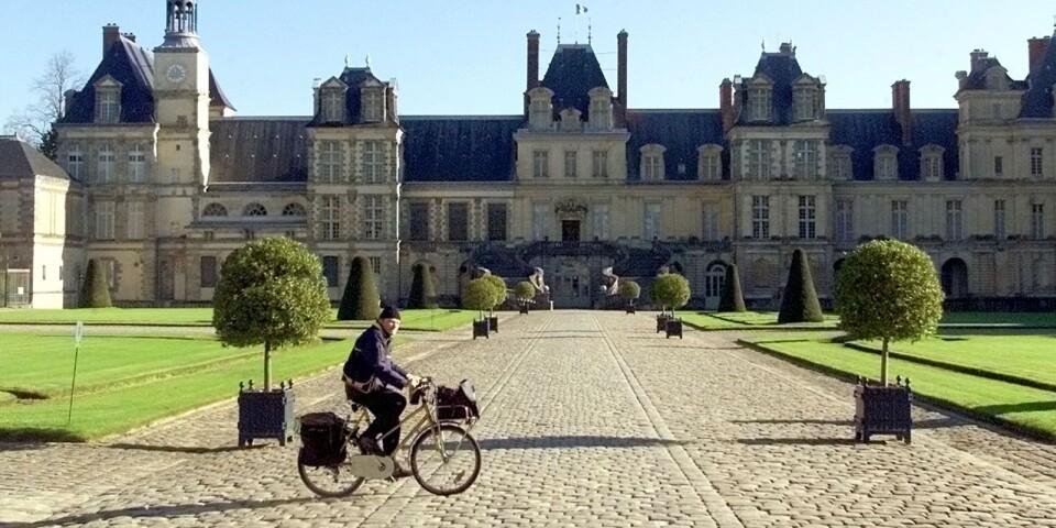 En brevbärare cyklar förbi slottet Fontainebleau, utanför Paris.