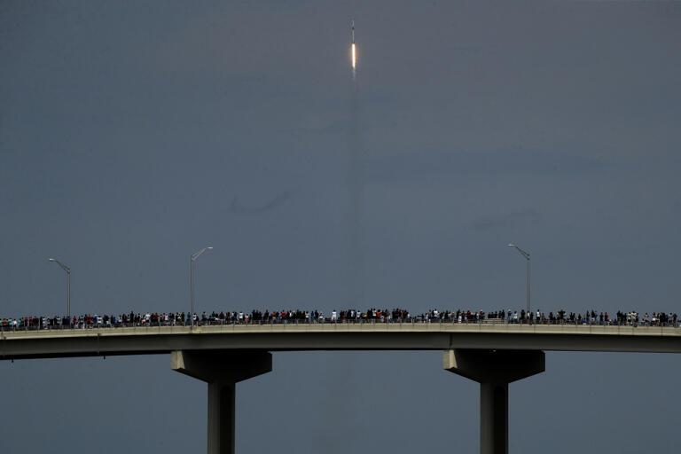 Raketuppskjutningar är ett folknöje i Florida, även i covidtider. Här beundrar samlade åskådare den stigande Falcon 9-raketen från en bro i Titusville.