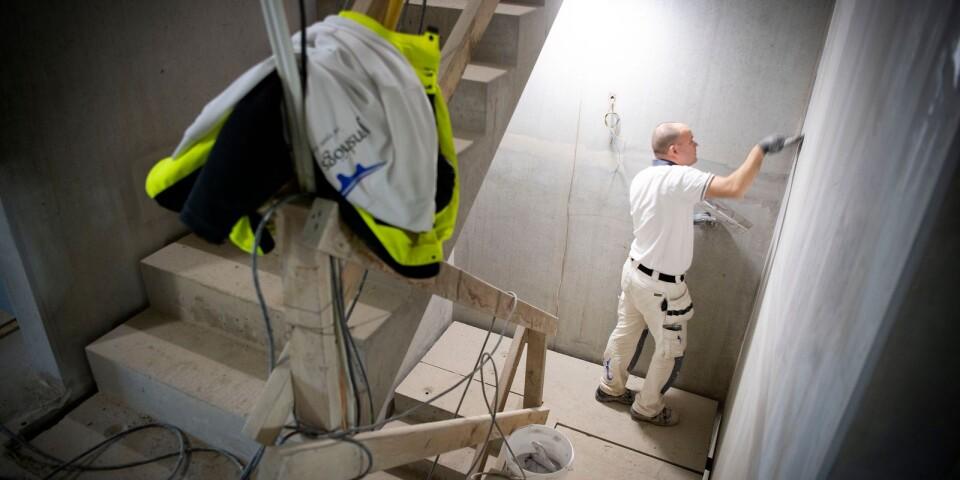 Markus Bengtsson spacklar väggarna i den framtida trappuppgången.