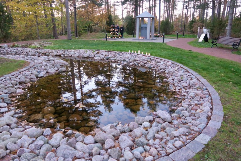 På den nya askgravlunden på Västra begravningsplatsen möts besökaren av en vattenspegel innan gravpaviljongen i granitsten, som namnplattorna sitter på.