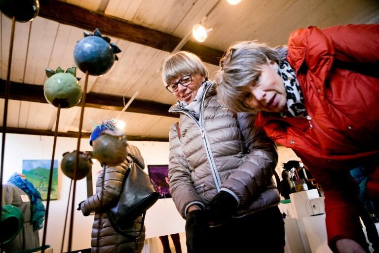 """Två besökare tittar på Maria Magnussons verk """"Mariablomma"""" på Mästers galleri vid Svaneholms slott i Skurup."""