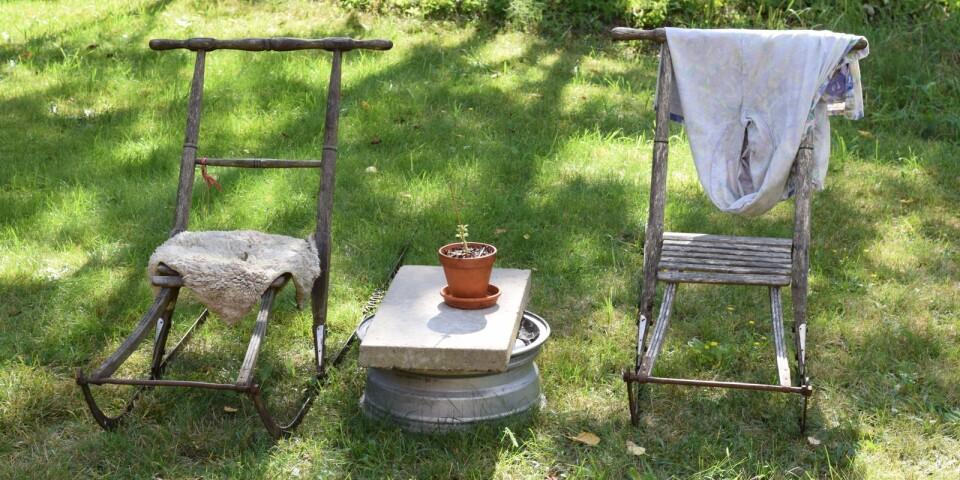 Kälkar som sittplatser i trädgården. På vintern har Marianne en liten kälkuthyrning.