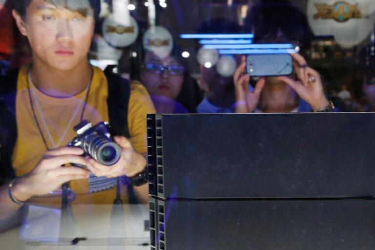 Människor tar bilder på konsolen Playstation 4 vid Tokyo Game Show 2013. Jättarna Sony och Microsoft får i år visa upp sina kommande tv-spelskonsoler på andra sätt.