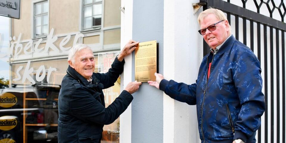 Lennart Nilsson och Håkan Hasslöf visar var den nya minnesplattan ska sitta.  Minnesplattan berättar Sjögrenska gårdens historia och är en donation av Oscar Nilssons döttrar.