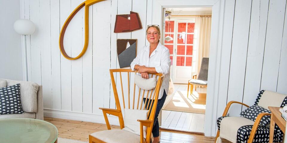 Åsa Hjelm står i vardagsrummet. På väggen hänger ett konstverk av Manfredo de Souzanetto.