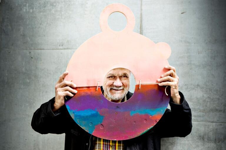 """Enno Hallek spexar under hängningen av konstutställningen No bad days på Kalmar konstmuseum år 2015. Han håller en av sina """"bärbara solnedgångar""""."""