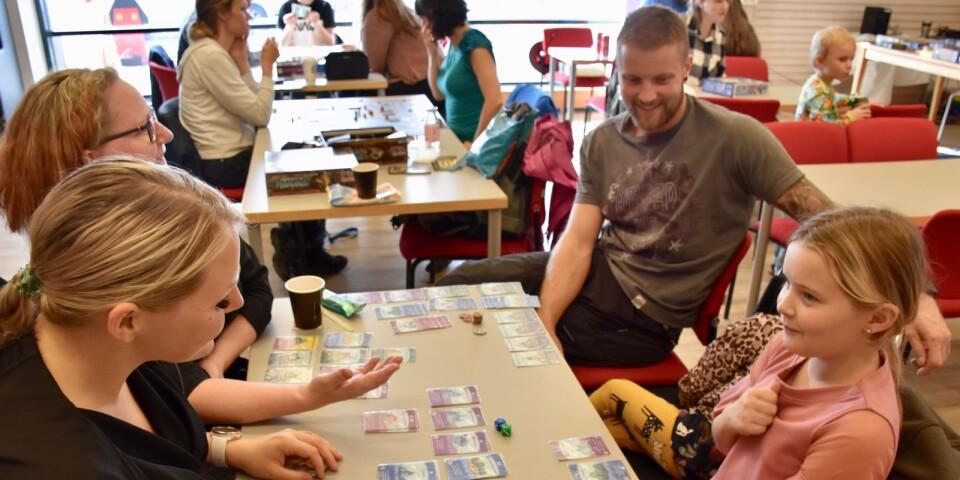Ebba Alhage (närmast till höger)  med lillasyster Wilda Alhage, pappa Jens Alhage, mormor Ylva Larsson och  mamma Gisela Tommysdotter Alhage (längst fram till vänster). De spelade Machi Koro, ett spel där man byggde en stad.