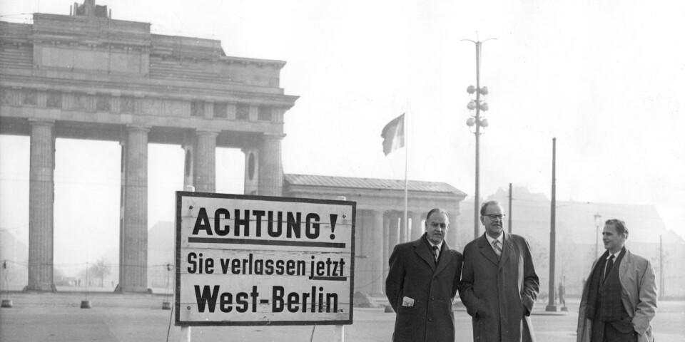 Statsminister Tage Erlander (S) och hans assistent Olof Palme vid gränsen till Öst-Tyskland, DDR, med Brandenburger Tor i bakgrunden i samband med det tyska SPD:s kongress 1958.