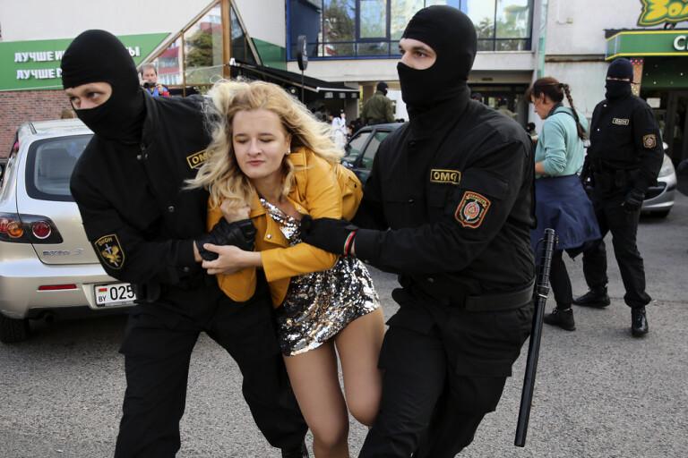 Belarusisk kravallpolis griper en demonstrant under lördagens demonstration i huvudstaden Minsk.