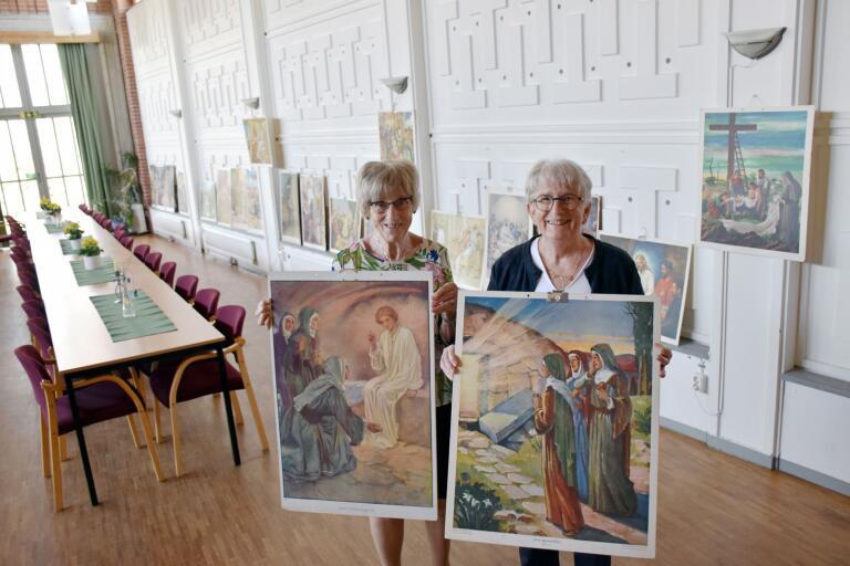 Iréne Karlsson och Lena Gellenmyr håller upp planscher som föreställer Jesus uppståndelse. Planscherna användes förr i skolundervisningen.