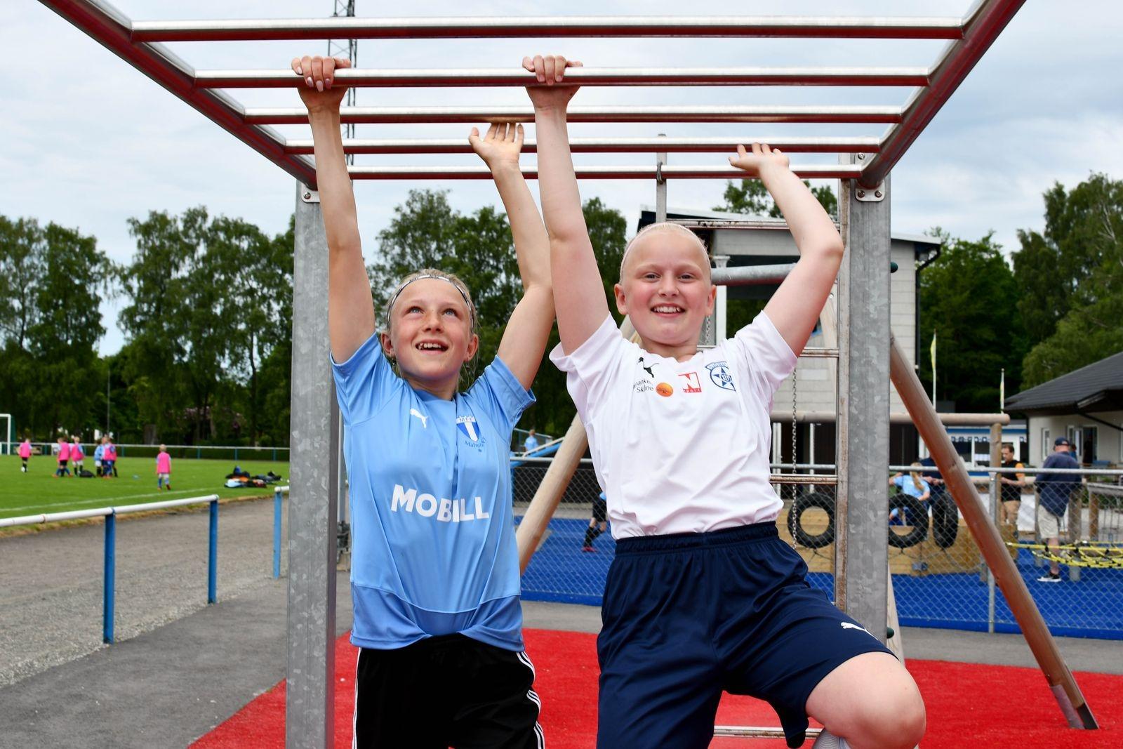 """Wilma Ceder och Hilda Eriksson hänger på motorikbanan under lunchpausen. """"Bäst med lägret är chansen att få lära sig nya saker av duktiga tränare"""" säger Wilma."""