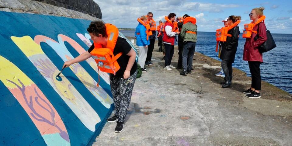Emelie Hansson från Kivik fyller i ögat på havsvidundret i bokstaven M. Målningen ör ett samarbete mellan Simrishamns hamn, gatukonstnätverket Street Corner, föreningen Grunden SÖSK och LSS-verksamheten i Simrishamns kommun.