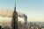 Bakom Empire State Building syns tvillingtornen brinna efter flygplansattackerna för 20 år sedan, 2001.