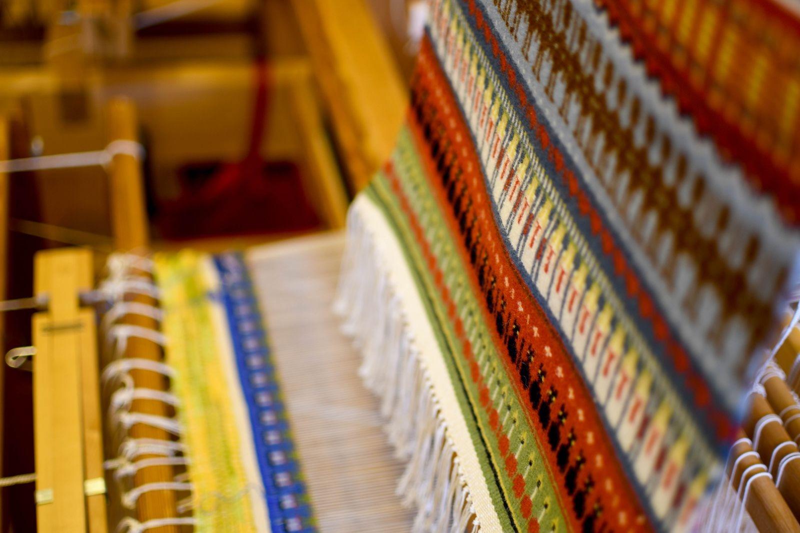 I vävstolarna skapas inte bara vackra dukar och handdukar utan även ponchos, sjalar, plädar och underlägg. På bilden syns ett gubbatäcke.
