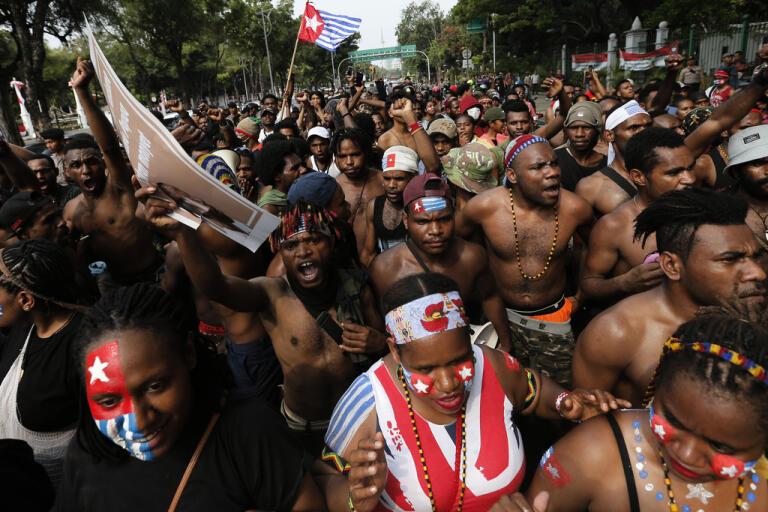 Papuanska studenter ropar slogans under en demonstration mot rasism utanför presidentpalatset i Jakarta i augusti 2019.