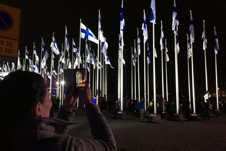 Invid Salutorget i Helsingfors klockan 18 på tisdagskvällen: barn hissade 100 finska flaggor innan nationalsången sjöngs i lätt snöfall. Foto: Lars Näslund.