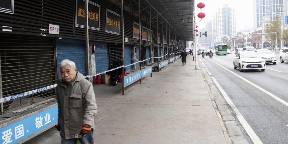 En man passerar den igenbommade marknaden i Wuhan i Kina, där utbrottet av det sarsliknande viruset tros ha börjat.