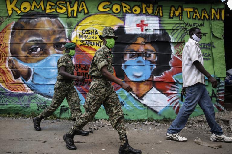 Folk passerar förbi en väggmålning med coronamotiv i slumområdet Mathare utanför huvudstaden Nairobi i Kenya. Arkivbild.