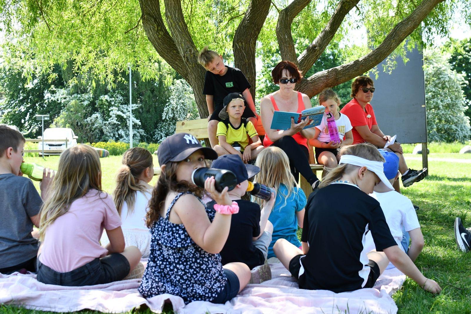 Efter en förmiddag med fartfyllda aktiviteter slog sig förskoleklassen ner i skuggan under ett träd för att ta en välförtjänt paus och lyssna på en spännande berättelse.