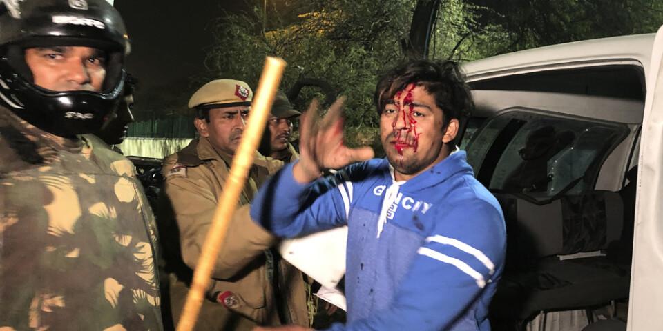 Polis griper en skadad student utanför universitetet Jamia Millia Islamia i Delhi, Indien. Bild tagen söndag 15 december.