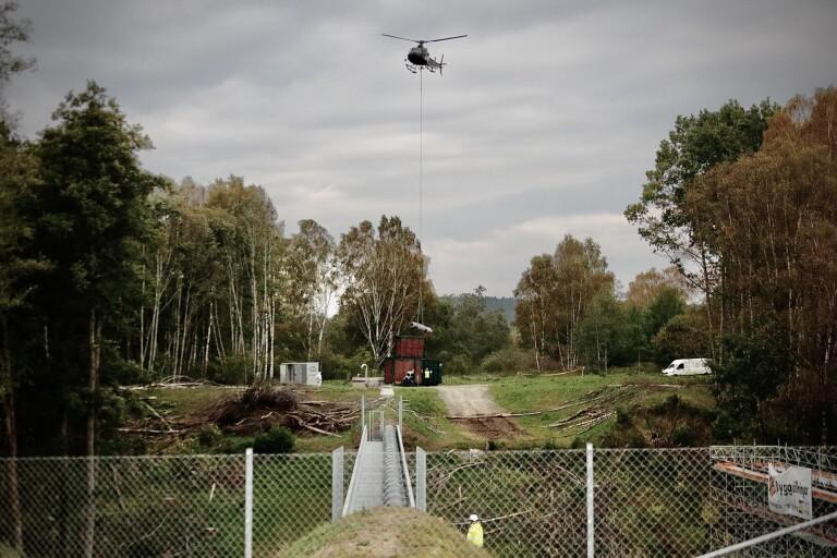 Helikoptern flög strax över trädtopparna när den lyfte upp den gamla rörbron och sedan släppte ner den i en container.