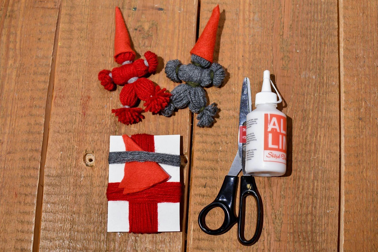Du behöver: Sax, lim, en bit kartong, garn och en liten bit filttyg. I museets pysselpåse kommer garnet färdigupplindat, annars börjar du med att linda upp garnet i två olika längder runt en bit kartong. Cirka 40 varv till kroppen och 30 till armarna.