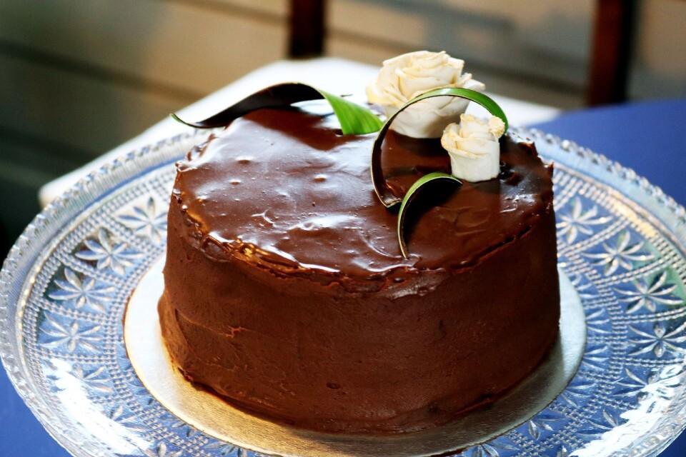 En chokladtårta med kola, ingefära och citron, toppad med marsipanros och gröna blad av choklad.