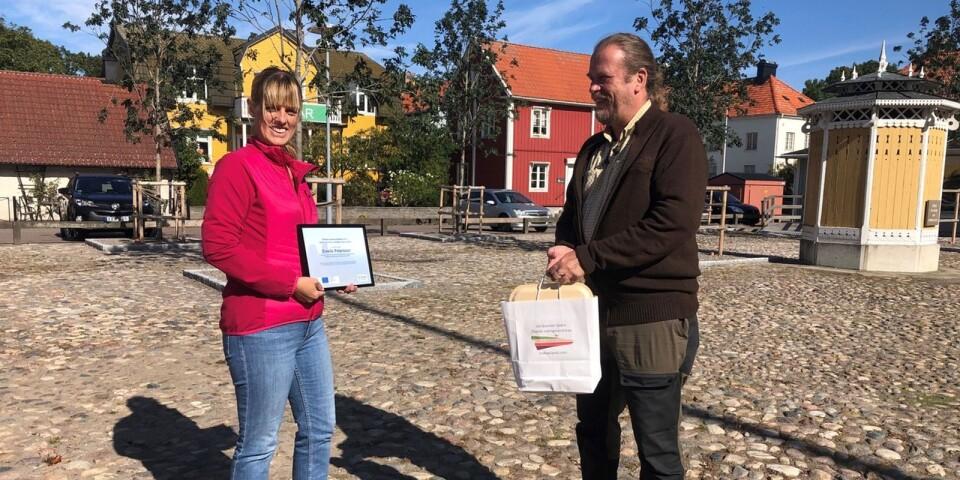Emelie Petersson och projektledaren Lars Wellin vid prisutdelning på torget i Mörbylånga.