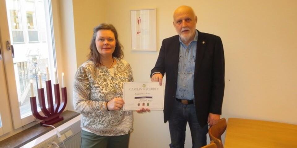 Ordförande i Caritas, Frimurarlogerna i Kalmar, Peter Adolfsson, delar ut 50 000 kronor till Kvinnojouren