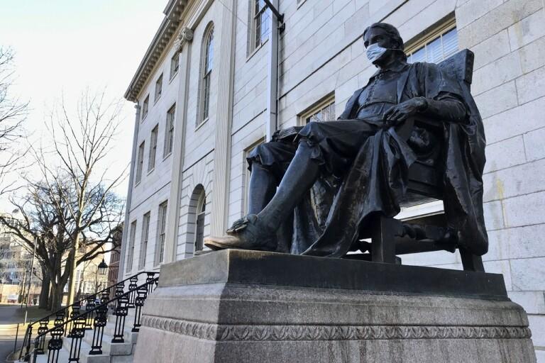 Den välkända John Harvard-statyn på universitetets campus i Cambridge har också fått ett munskydd. Arkivbild.