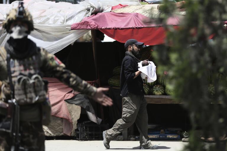 Afghansk säkerhetspersonal med ett spädbarn i famnen efter attacken mot en förlossningsklinik i Kabul den 12 maj i år.