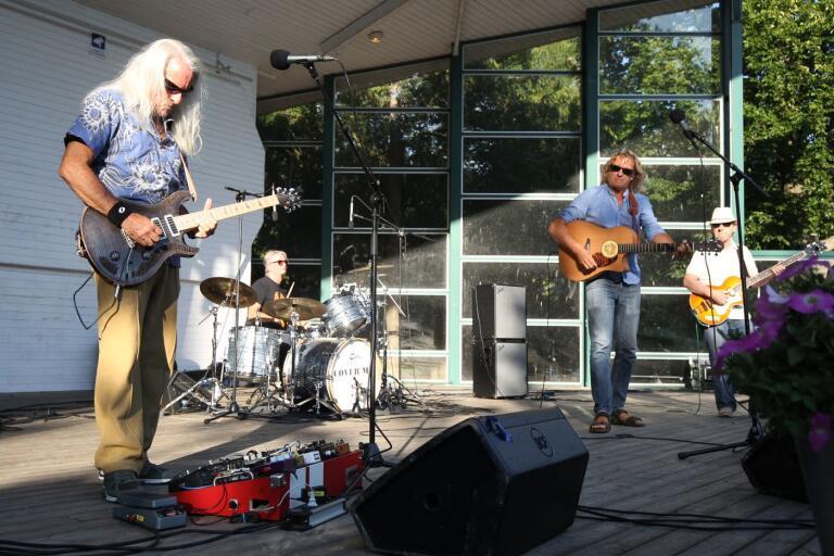 Gitarristen i Cover me river av ett glamrocksdoftande solo inför de trehundra åhörarna i stadsparken.