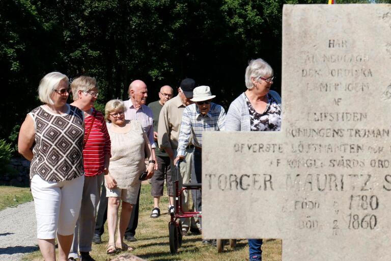 Anna-Lena Hultman visar och berättar om gravstenar på Hössna kyrkogård.