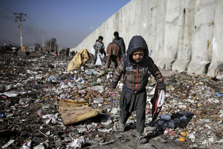Ett barn letar efter bränsle på en soptipp i Afghanistans huvudstad Kabul.