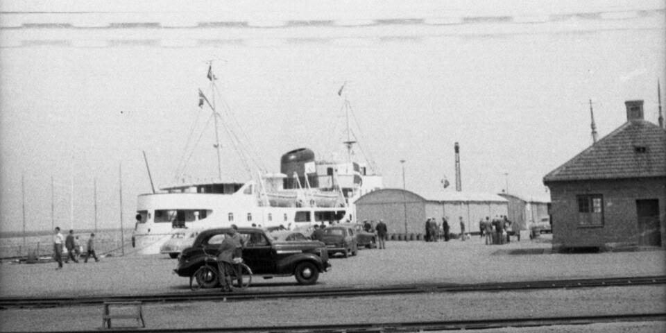 En färja har lagt till i hamnen. Vilka linjer trafikerades från Simrishamn? Till vad användes husen som syns i bild?