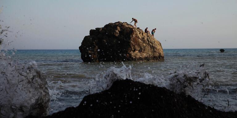 Människor badar från en klippa nära staden Pafos på Cypern. Arkivbild från juli i år.