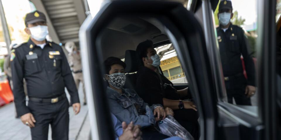 En polis stannar ett fordon i Bangkok för att kontrollera att förare och passagerare inte har feber.