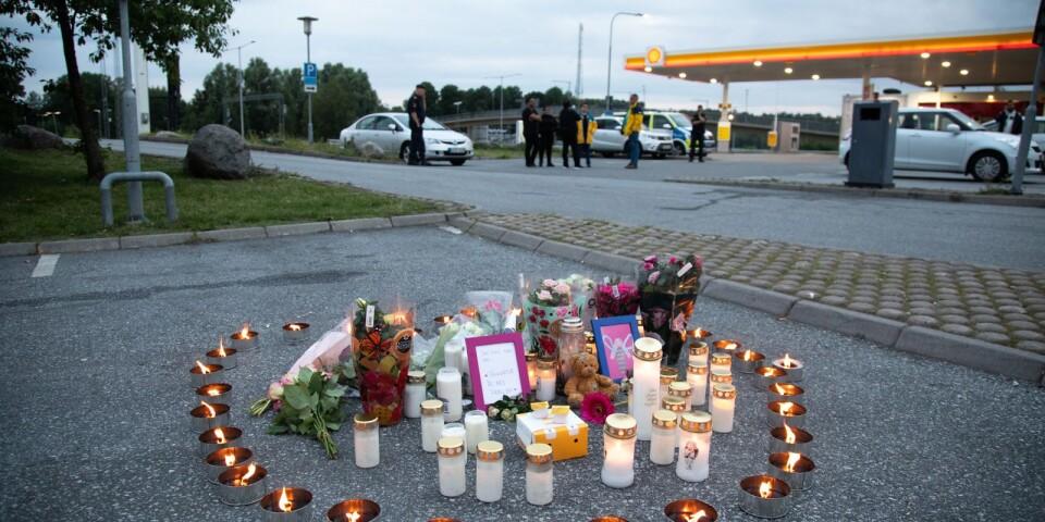Blommor och ljus på platsen där en tolvårig flicka skottskadades söder om Stockholm natten mot söndagen. Flickan avled senare på sjukhus