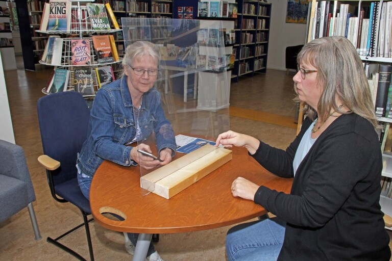 En plexiglasskiva sätts upp mellan besökaren och personalen vid internet drop in på Herrljunga bibliotek. Bibliotekschef Eva-Lena Liljedahl, till vänster, och bibliotekarie Carina Svensson Harju visar.