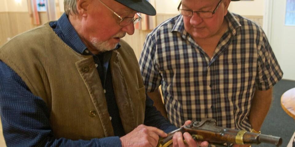 Ett äkta mordvapen. Erland Berg visar Huskvarnapistolen, som han hittat hos en släkting i Gullspång, för sin syssling Kaj Gustavsson. Det är ett jordnära krönikespel där många på och utanför scenen har kopplingar till de inblandade i 1800-talsdokumentären.
